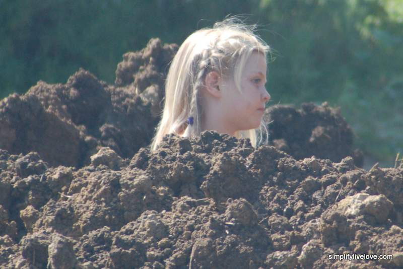 Anna's head sticking up out of pile of dirt
