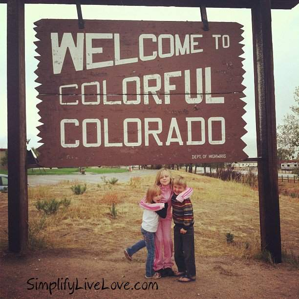 kids under the welcome to colorful colorado sign