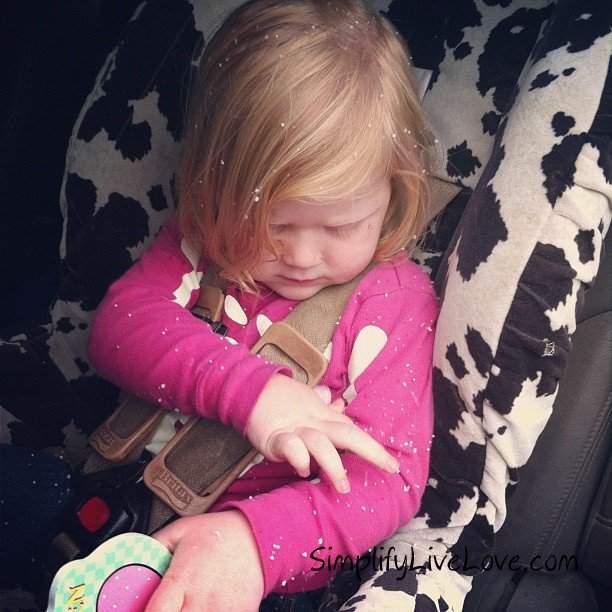 girl in car seat examining snow flakes