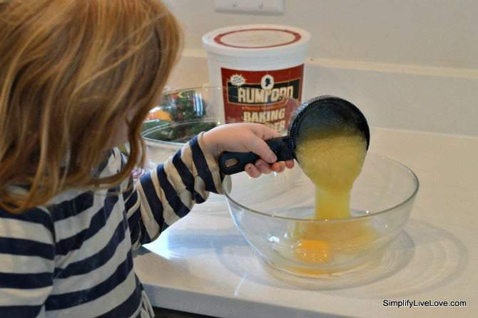 measuring out applesauce for applesauce muffins