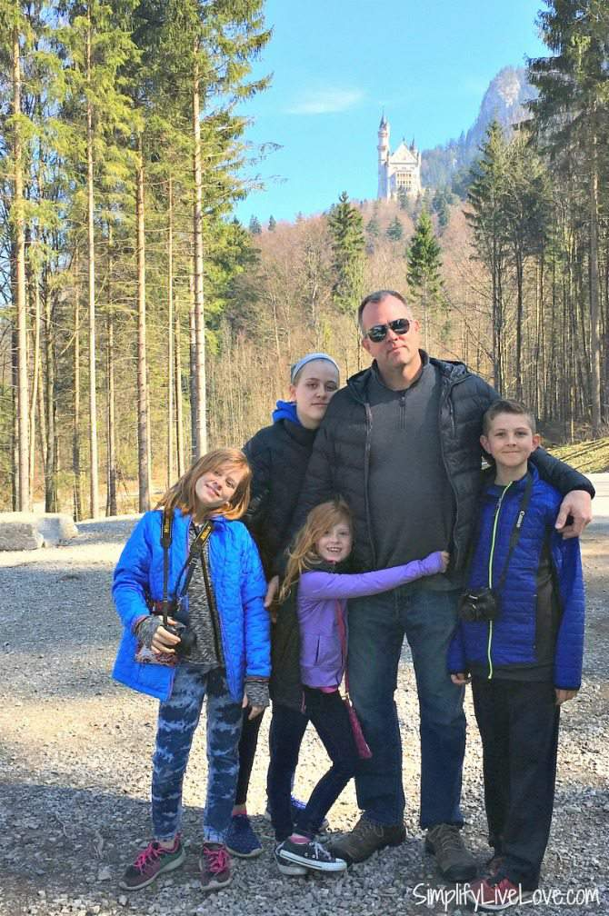 4 kids and they're dad standing on the path to Neuschwanstein.