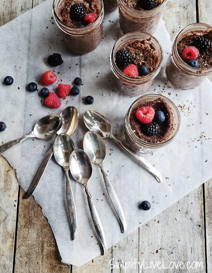 5 jelly jars of instant pot chocolate pudding, spoons, and berries