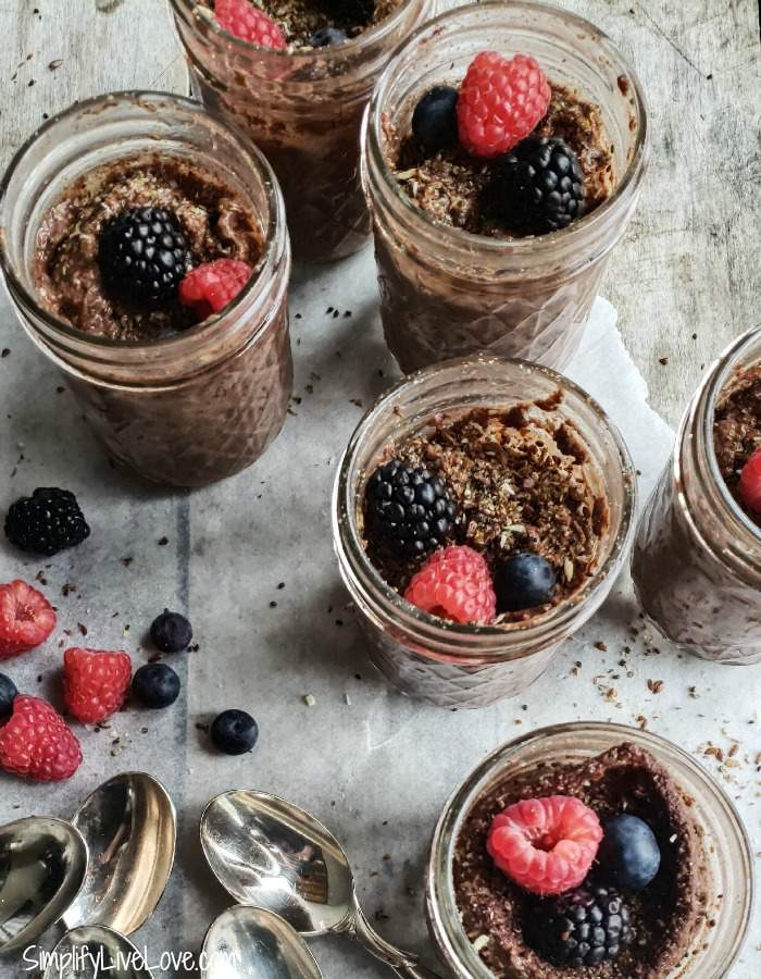 jars of healthy instant pot chocolate pudding with fresh berries