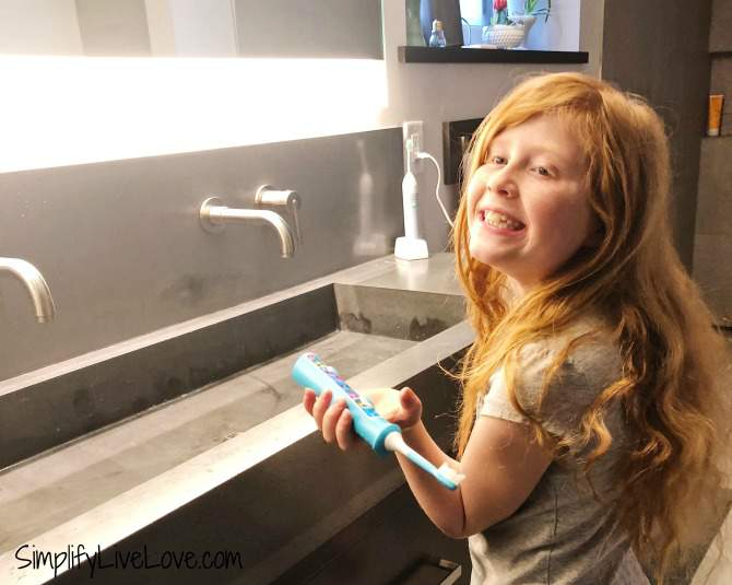 red headed girl brushing her teeth with natural toothpaste for kids