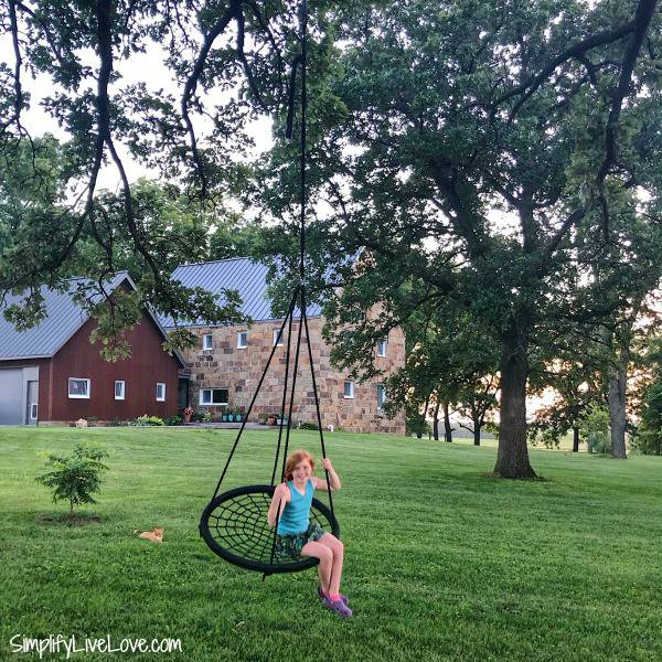 girl on swing in front of minimalist house
