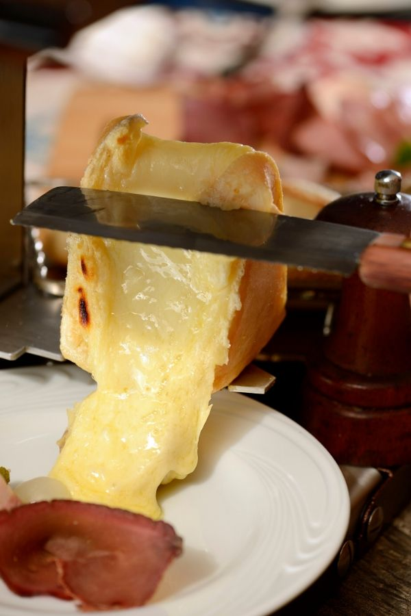 scraping melted raclette cheese onto a plate